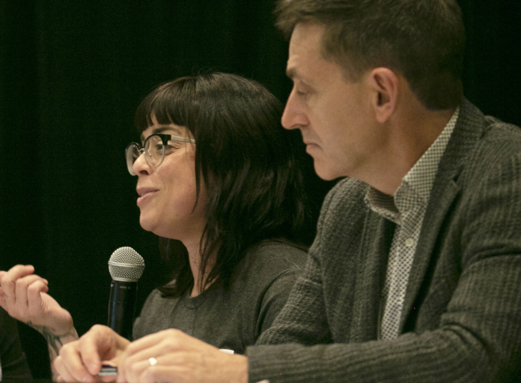 A woman and man speaking on a panel