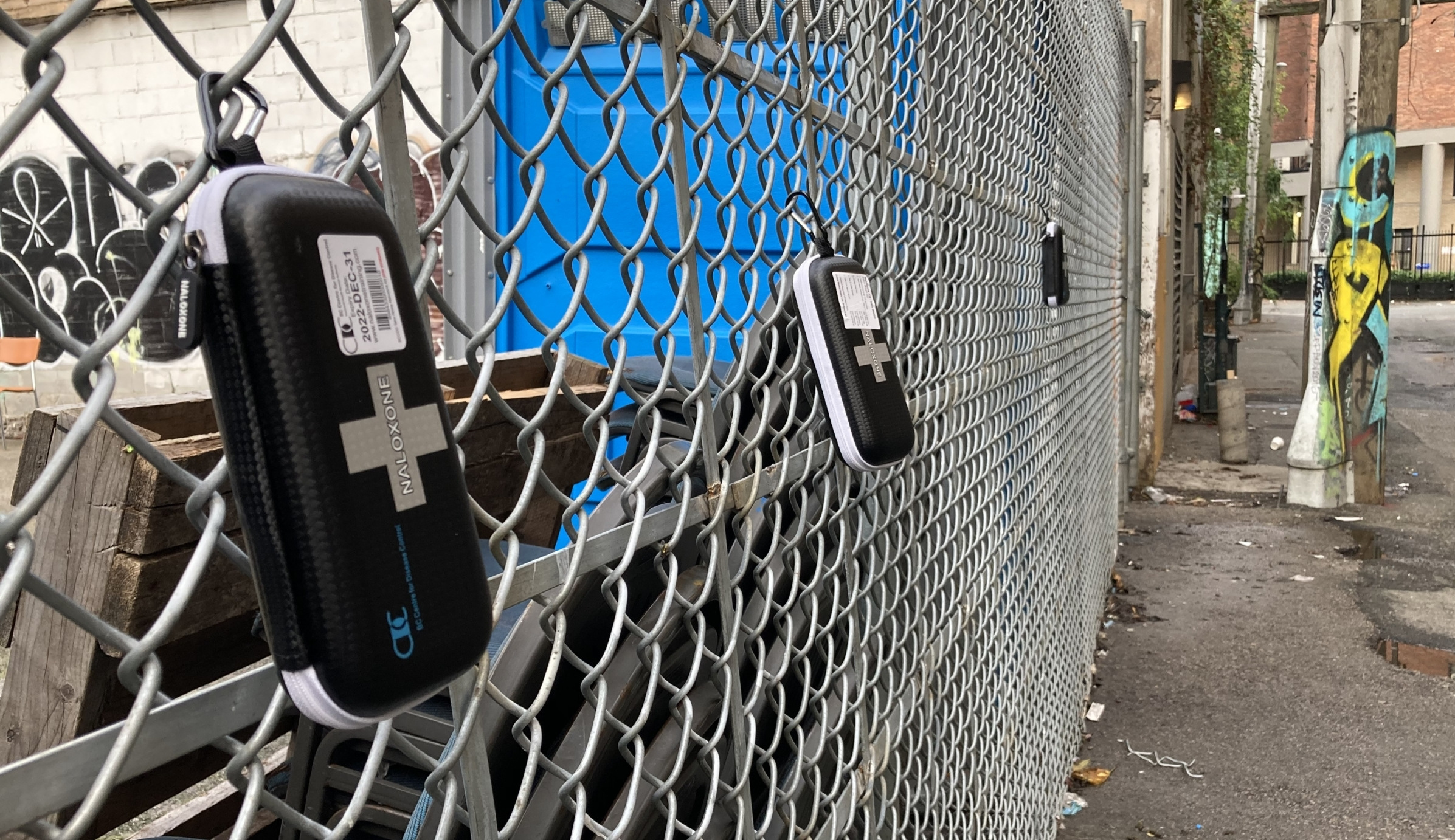 A narcan kit hanging on a chain link fence
