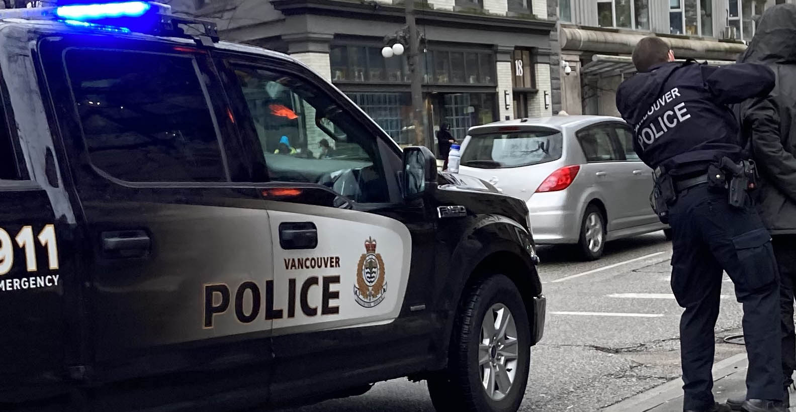 Two police officers arresting someone on the sidewalk in Vancouver