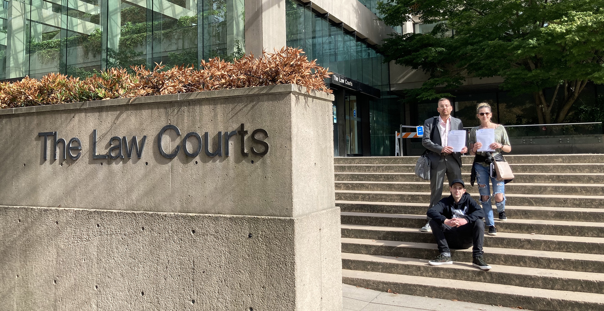 three people standing on the steps of BC supreme court